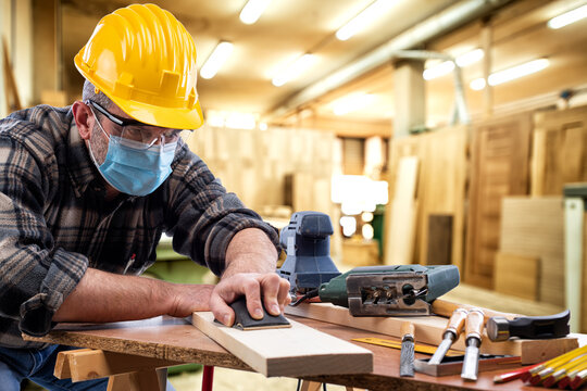 Carpenter worker at work in the carpentry workshop, wears helmet, goggles and surgical mask to prevent coronavirus infection. Preventing Pandemic Covid-19 at the workplace.
