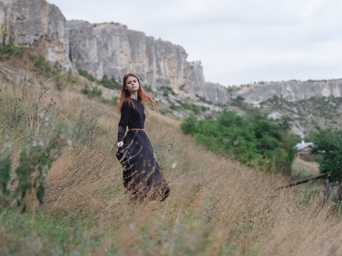 woman traveler in a black dress runs on dry grass in the meadow and mountains in the background