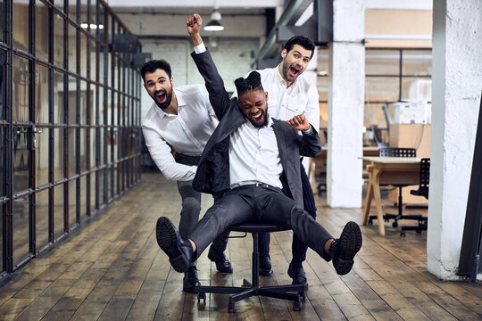 Work hard play hard. Four young cheerful business people in formal wear having fun while racing on office chairs and smiling.