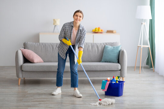 Pretty young lady wiping floor with mop, doing house cleanup, free space. Professional sanitary service concept