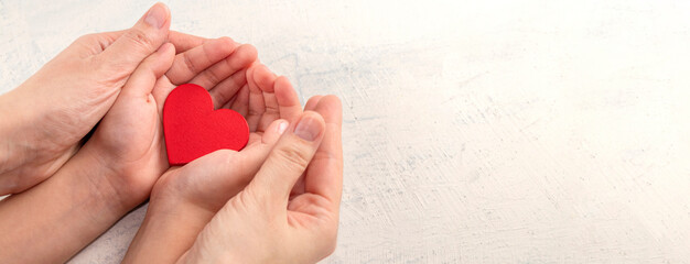 Obraz Children and mothers hands holding red heart on white textured background. Concept of health care, love, organ donation, mindfulness, wellbeing, family insurance - fototapety do salonu