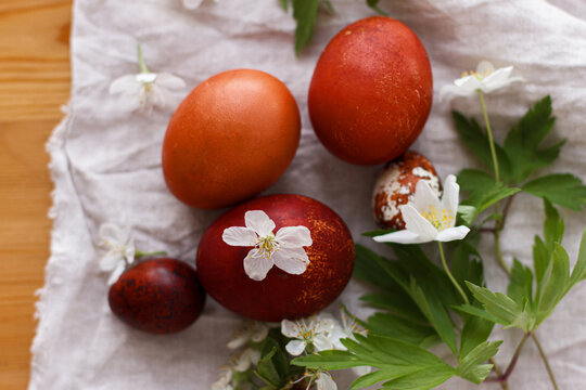 Modern red easter eggs with spring flowers on rustic linen cloth on wooden table. Happy Easter!