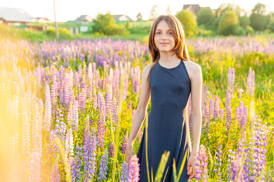 Happy teenage girl smiling outdoor. Beautiful young teen woman resting on summer field with blooming wild flowers green background. Free happy kid teenager girl childhood concept