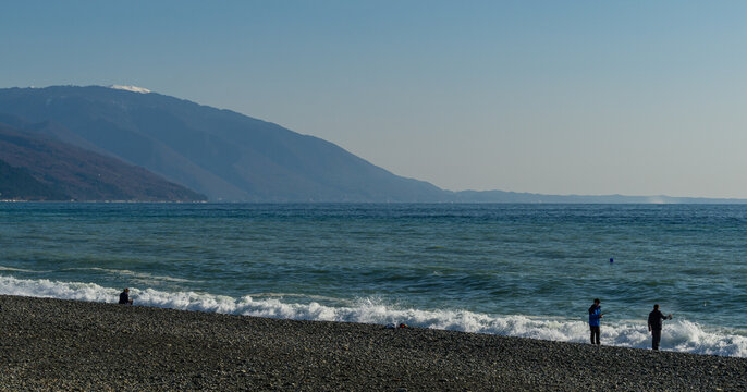 Fishermen are fishing in Black Sea. View of Caucasian mountains in Abkhazia from Russian side. December winter sea in southern resort of Russia. Sunny winter day. Sochi, Russia - December 08, 2020