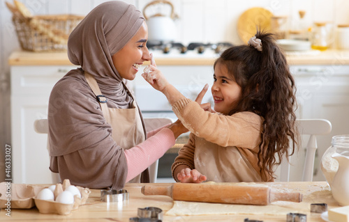 Mother's Day Concept. Little Girl Having Fun With Muslim Mom In Kitchen