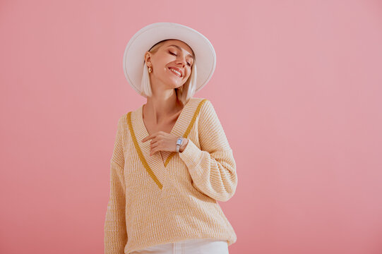 Happy smiling woman wearing trendy yellow v-neck sweater, white hat, elegant wrist watch, posing on pink background. Spring fashion conception. Copy, empty space for text