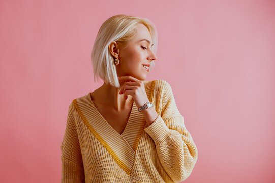 Happy smiling woman wearing trendy yellow v-neck sweater, elegant silver wrist watch, golden earrings, posing on pink background. Spring fashion conception. Copy, empty space for text