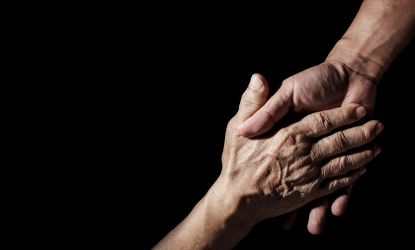 Senior health care provider. Home care for mature people. The caregiver makes elderly feel safe. Concept of family assistance and helping older adults. The aged wrinkled skin hand on black background.