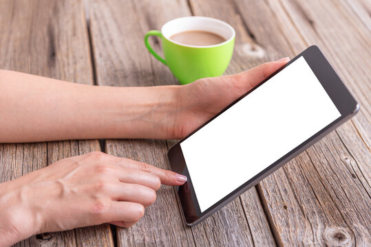 Tablet in hands on a wooden table with a cup of coffee.