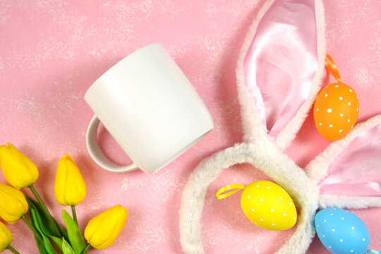 Easter product mockup with bunny ears and easter eggs on pink background flatlay. White coffee mug mock up with negative copy space for your text or design here.