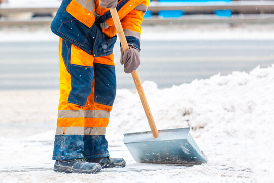 Communal services worker sweeps snow from road in winter, Cleaning city streets and roads during snowstorm. Moscow, Russia.