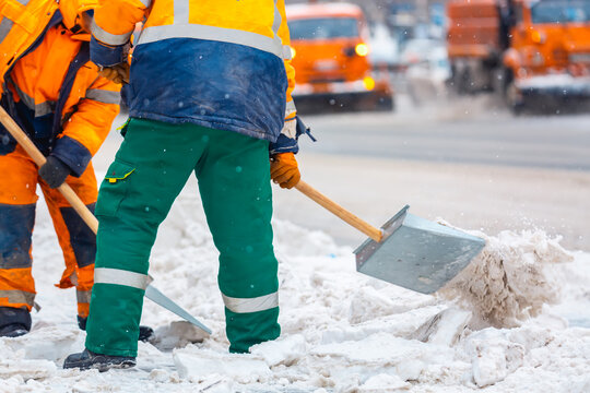 Communal services workers sweep snow from road in winter, Cleaning city streets and roads during snowstorm. Moscow, Russia.