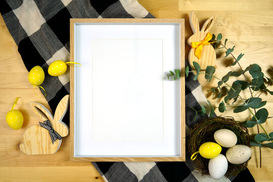 Easter Farmhouse theme product flatlay mockup with buffalo plaid and wood bunnies. White frame mock up with negative copy space for your text or design here.