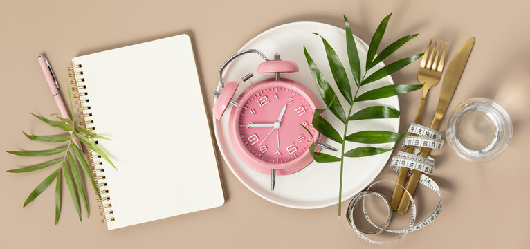 Composition with cutlery, measuring tape, blank paper notebook, water, tropical leaves and alarm clock on color background. Diet concept, copy space