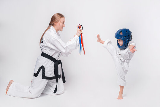 Mother her little son practicing martial arts over white background.