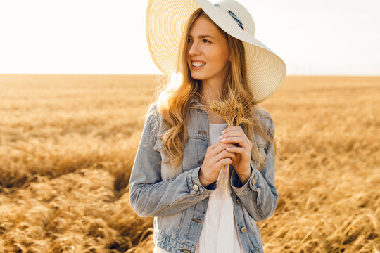 Attractive young woman in wheat field at sunset