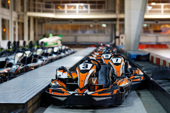 Kart cars parked one by one on indoor go-kart racing track in anticipation of drivers. Shallow focus.