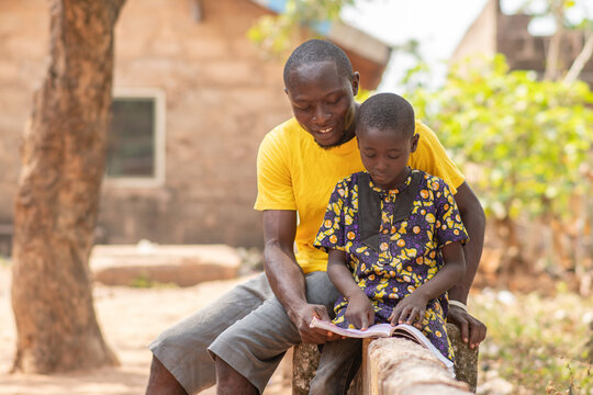 african man teaching a child, helping with home work