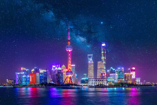 Cityscape of Shanghai at twilight sunset with stars and Milky Way. Panoramic view of Pudong business district skyline from the Bund.