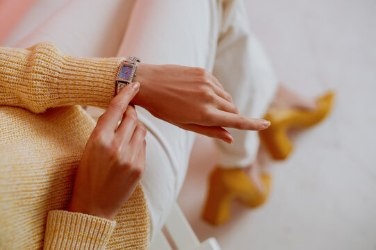 Close up fashion details: silver wrist watch on elegant woman` s hand. Model wearing trendy spring outfit. Copy, empty space for text