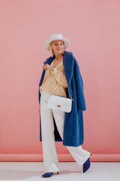 Happy smiling fashionable woman wearing trendy blue faux fur midi coat, yellow sweater, wide leg white jeans, hat, pointed toe shoes, holding small leather bag, posing on pink background