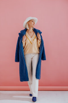 Happy smiling fashionable woman wearing trendy blue faux fur midi coat, yellow v-neck sweater, white jeans, hat, elegant wrist watch, pointed toe shoes, posing on pink background