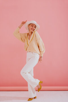 Happy smiling woman wearing trendy yellow v-neck sweater, white wide leg jeans, hat, pointed toe shoes, posing on pink background. Spring fashion conception. Full body portrait
