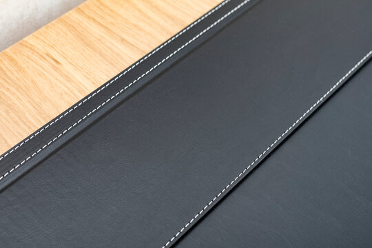 part of a black artificial leather stand on a wooden table. Background, texture