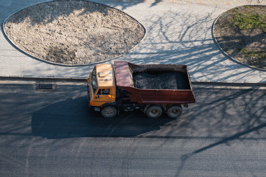 Truck with a breakstone on a road in the city during road construction work.