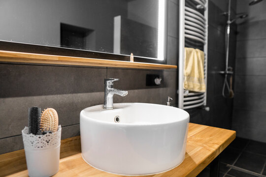 Bathroom interior with grey tile on a wall, stylish round sink and tap on a oak wood worktop. Minimalism in interior of bathroom.
