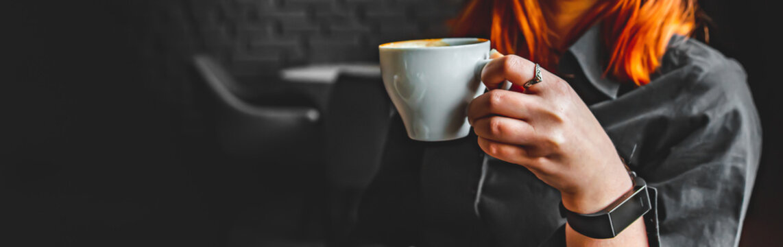 woman hands holding a white cup of tea or coffee in cafe