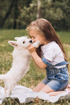 Adorable little girl holding plays with a puppy in the park