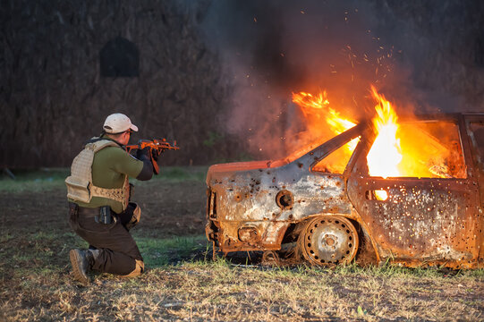 Army soldier hiding behind burning car shooting from machine gun. Action tactical combat