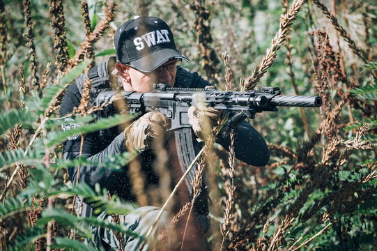 Army soldier shooting with rifle machine gun in the forest. Nature outdoor military combat training