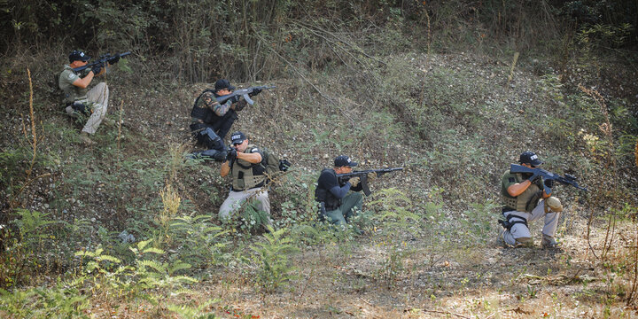 Army soldiers shooting with rifle machine gun in the forest. Nature outdoor military combat training