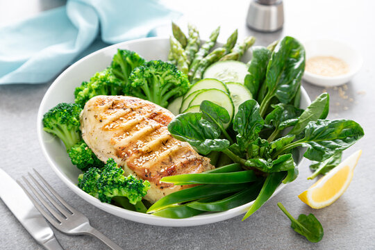 Chicken breast grilled, broccoli with asparagus and fresh green vegetables, spinach leaves in lunch bowl, healthy food