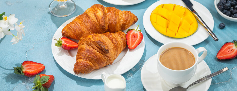 Luxury sunny continental breakfast on blue concrete background table with tropical plants shadows, banner