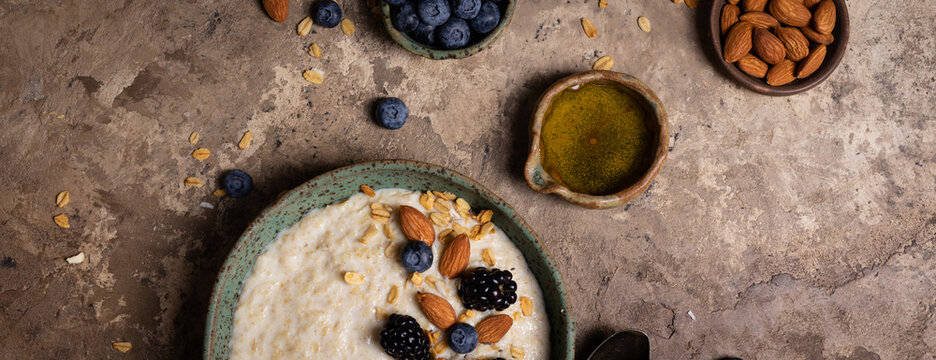 Oatmeal porridge with nuts, fresh berries and honey in a ceramic bowl on rustic background, banner