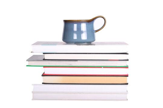 Books and a mug lie on a white background