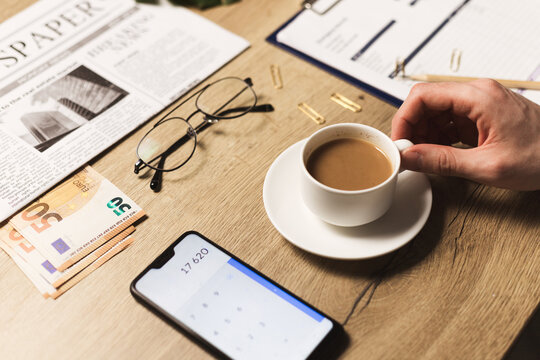 Businessman is calculating balance, expected profit or expenses with smartphone. Business plan and self accounting concept