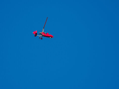 red gyroplane flies in the blue cloudless sky