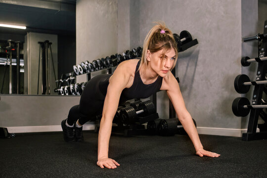 A woman in sportswear stands in the plank pose. Sportswear. Gym. Healthy lifestyle.
