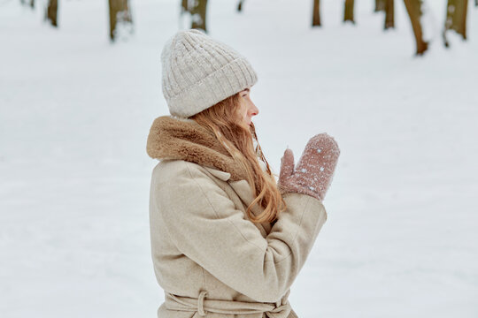 Side view of a woman in a knitted hat and coat with fur and looking away. Winter park with snow.