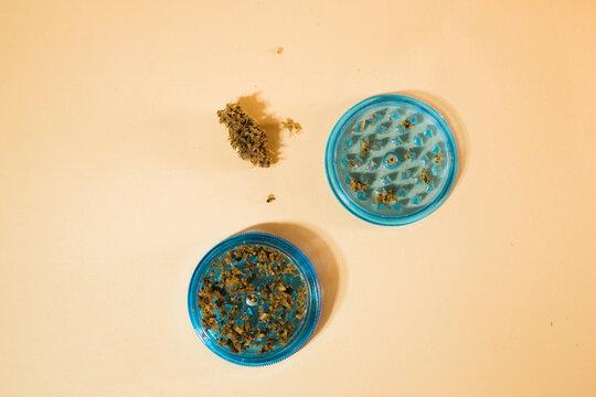 Marijuana bud in blue plastic grinder. Cannabis smoking. Flat lay