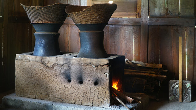 Traditional kitchen with firewood. There are two clay pans and a bamboo steamer on top. Classic kitchen of Indonesia