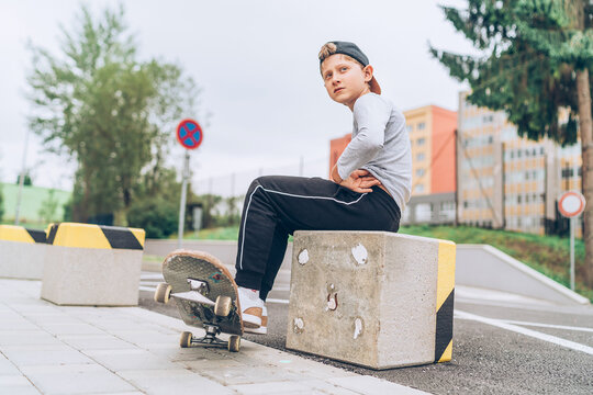 Teenager skateboarder boy portrait in a baseball cap with old skateboard on the city street. Youth generation Free time spending and an active people concept image.