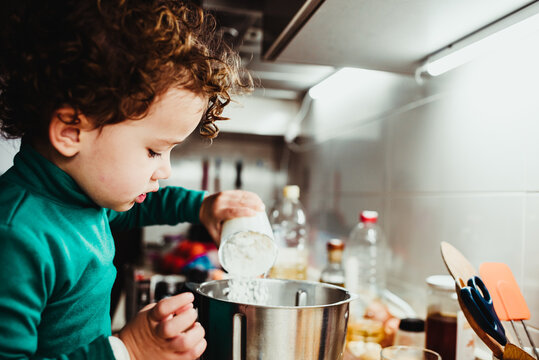 Two-year-old girl pours and mixes flour to cook dinner at home.