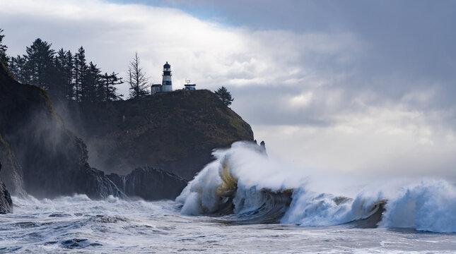 Huige waves crashing on the headland under Cape Disapointment lighthouse near the mouth of the Columbia River, Ilwaco, Washington