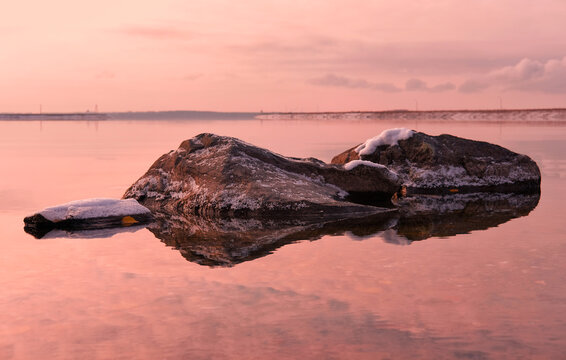 Stones covered by snow  on calm water background in early winter season on sunset.