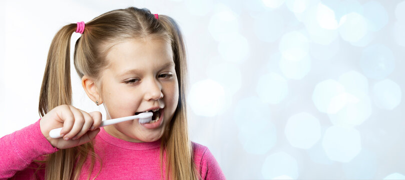 Preschool girl with first adult incisors and a toothbrush. The milk tooth has fallen out, and a permanent tooth grows in the open mouth. Dental hygiene concept